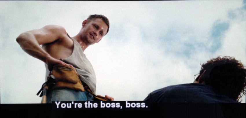 Curly-haired man looks up to sweaty Alexander Skarsgård in a shredder. Caption: You're the boss, boss