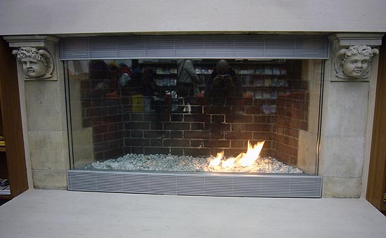 Fireplace with pebbled floor and small flame