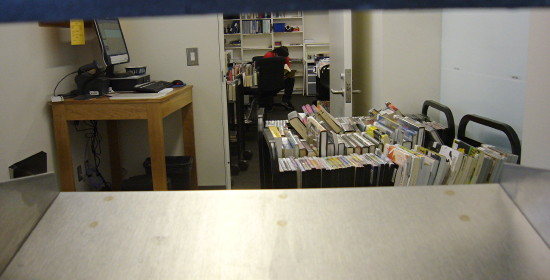 Carts of books and DVDs, a computer on a bench, and a distant staffmember seen through a blue and silver slot