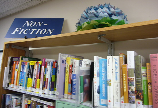 Paper chrysanthemum sits on top of bookshelf alongside NON-FICTION sign