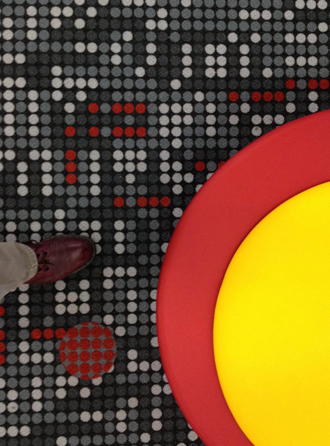 Black carpet with patterned dots; stool or concentric yellow and red circles