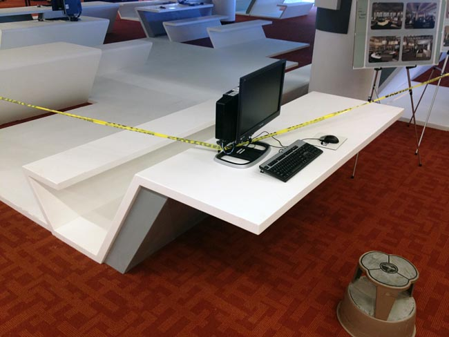 Off-the-shelf black Windows computer plunked atop custom-built Corian table