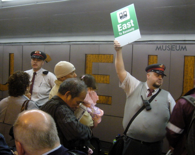 Supervisor in cap holds up green sign reading East To Kennedy