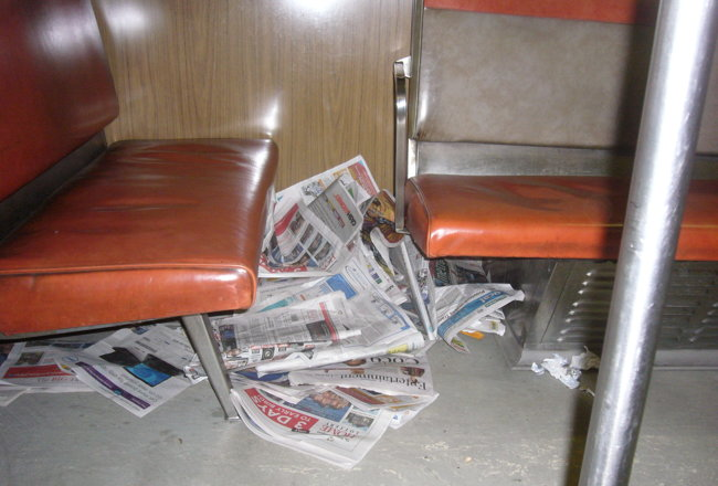 Large pile of newspapers under H4 subway-car seat