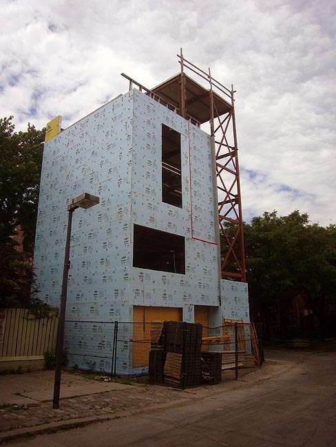Tall, narrow house under construction on deserted lot is covered in blue Tyvek sheets