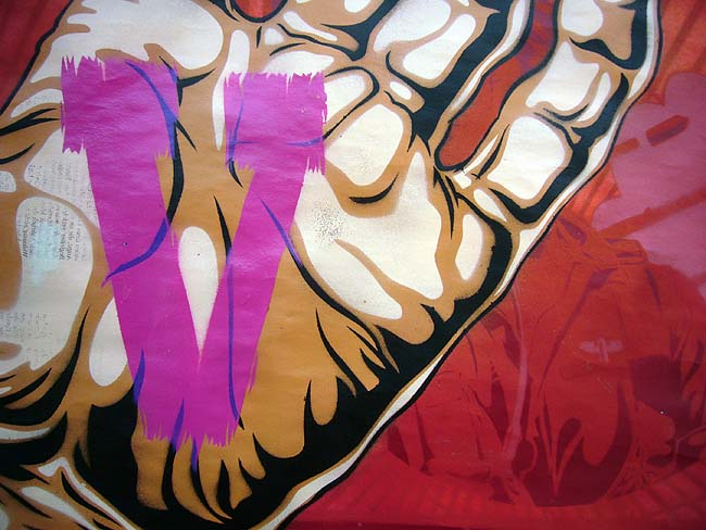 Pink painted V inside painting of cartoonish hand, all on ruby cartoonish background