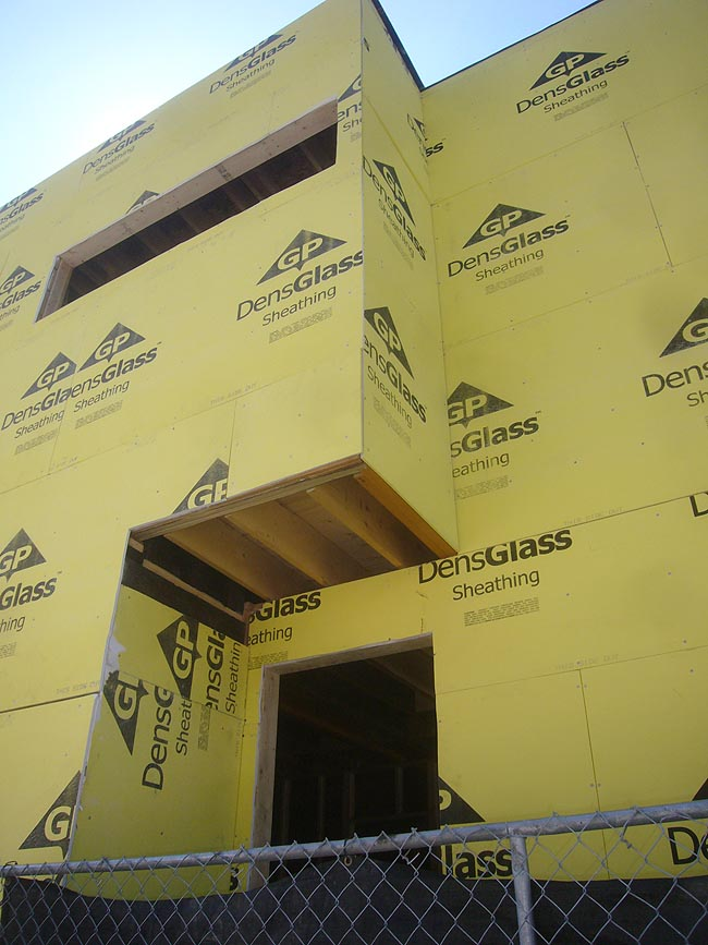 Walls and volumes of a house under construction are all covered in yellow DensGlass Sheeting