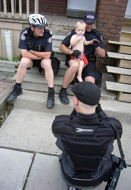 Two policemen pose with baby as young man in newsboy cap and motorcycle jacket snaps a picture