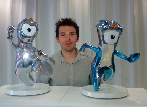 Man poses behind foot-high Wenlock and Mandeville trophies