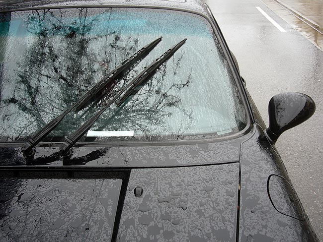 Black 911 with dual wipers grouped together in stationary position on rain-dappled windshield