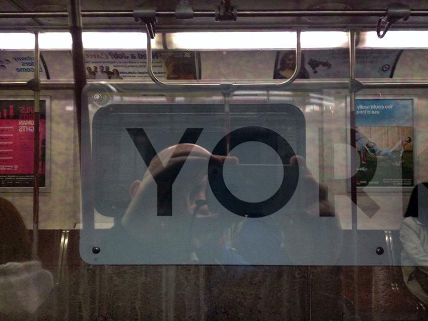 Subway sign YOR seen through reflective window