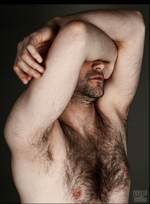 Hirsute man holds right arm crossed over his eyes, left arm resting on the right