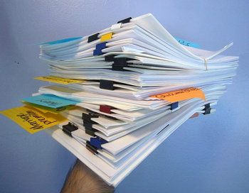 Hand holding eight-inch stack of papers with coloured alligator clips and Post-Its