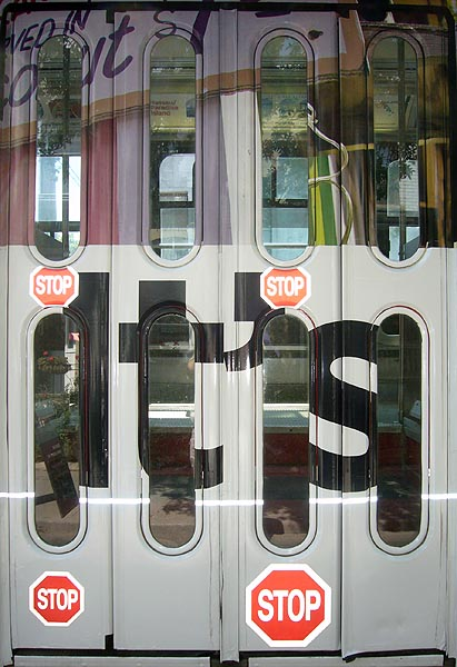 Streetcar doors have small STOP signs and the word it's with voids formed by the doors' windows