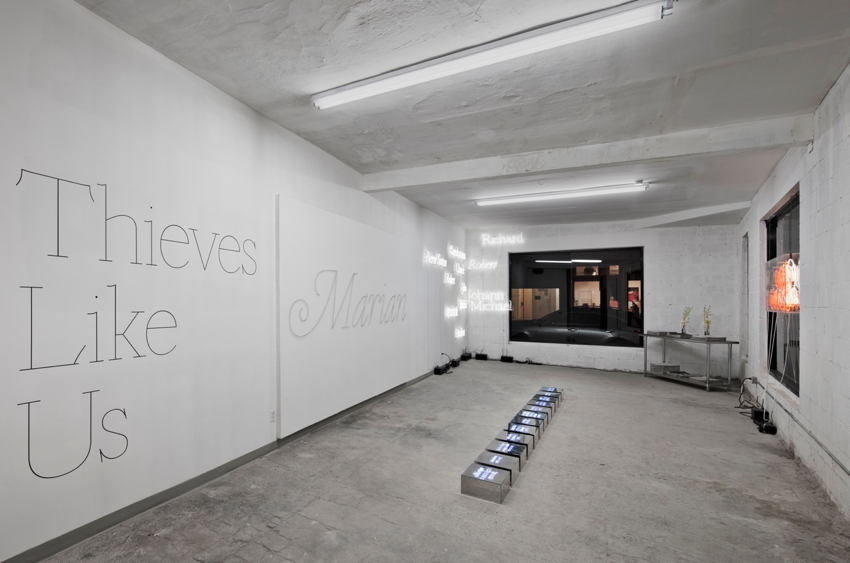 Gallery showing Thieves Like Us and Marian in giant monoline type on white walls