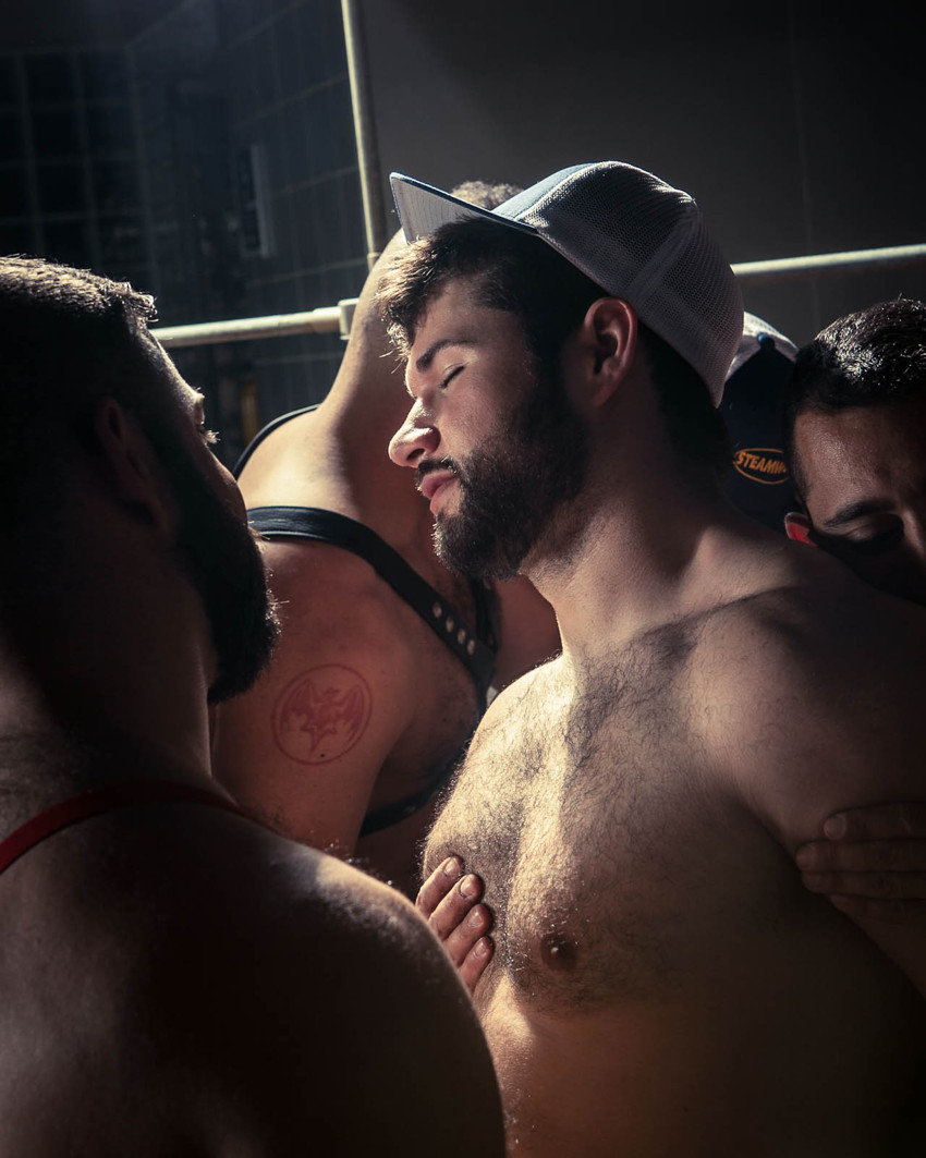 Young man, eyes shut and in a trucker cap, stands in a shaft of light in a throng of other men, one gazing at him, his own fingers pressed against his chest