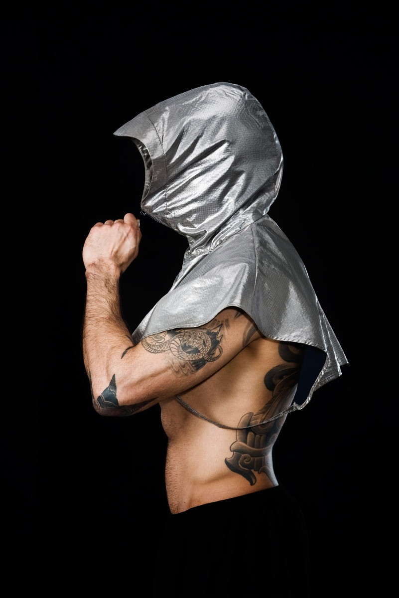 Muscular tattooed man in profile view with silver metallic ponch over head and shoulders