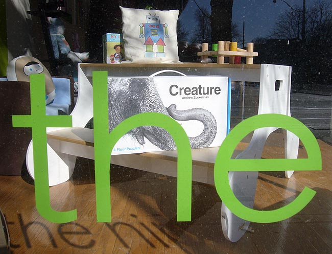 Store window has the word 'the' in green; inside the window sits a game package called Creature