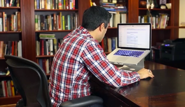 Man in plaid shirt hunched over desk working on a MacBook on a stand