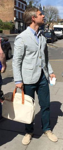 Martin Freeman in pale-blue streiped blazer, blue shirt, indigo pantalon, and bright beige nubuck shoes, with bone-colouted canvas bag with tan leather straps