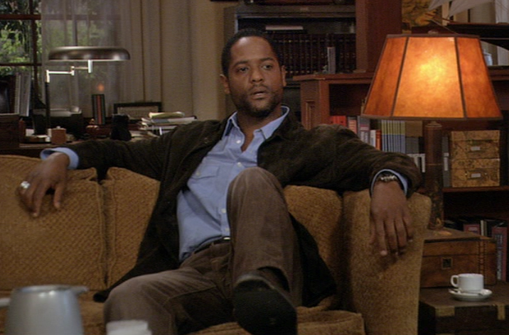 Blair Underwood in blue shirt and blazer, with conspicuous class ring and wristwatch