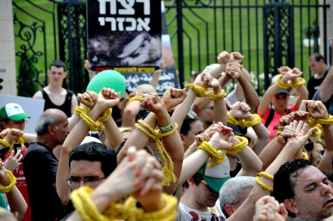 Protesters raise their hands over their heads, crossed wrists bound with yellow rope