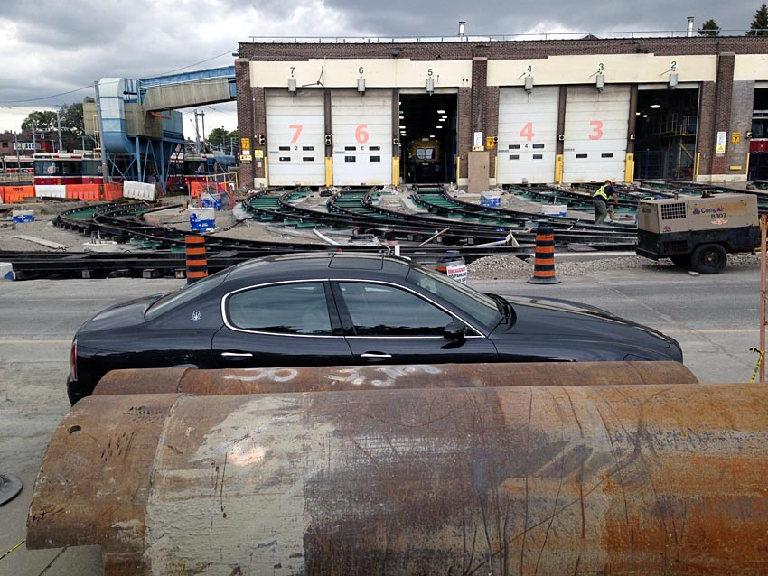 Maserati Quattroporte parked between giant rusted sewer pipes and rear tracks at Russell Yard under construction