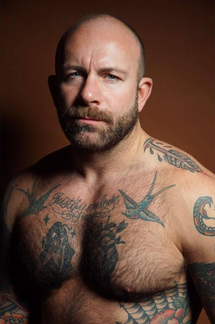 Severely tattooed muscular baldie against bronze background