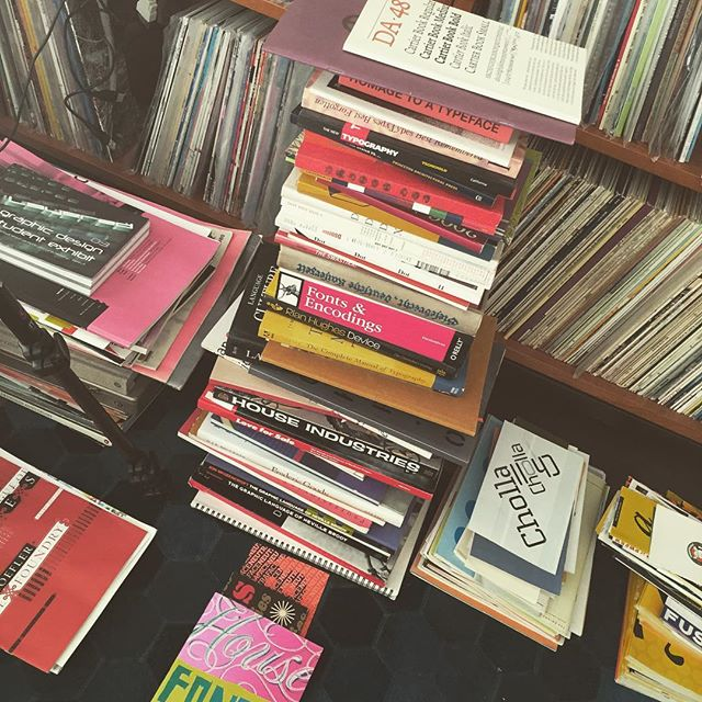 Piles of printed matter in front of LP-record shelves