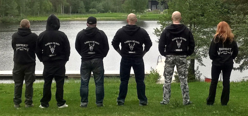 Five guys in Soldiers of Odin sweatshirts (and one red-haired girl), backs turned