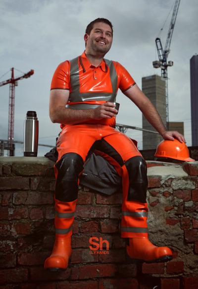 Man sits on ledge wearing lurid orange-and-black rubber shirt, work trousers, and boots, with his hand resting on equally lurid orange hardhat