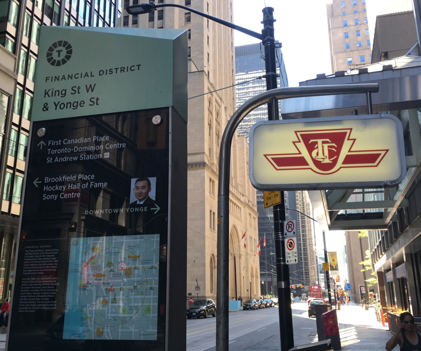 Monolithic sign with green cap (with an angled top edge) next to illuminated TTC sign