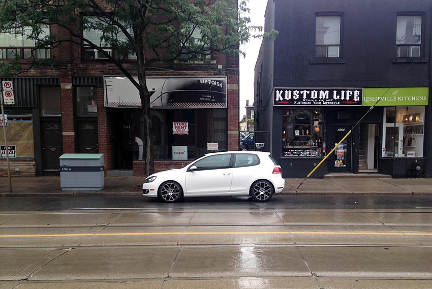 Lone Golf GTI on a rainy street, with Kustom Life storefront sign nearby