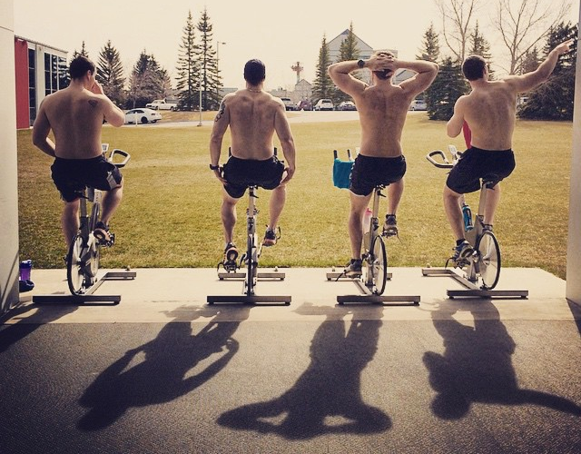 Four shirtless men on exercise bikes at a garage-door ramp