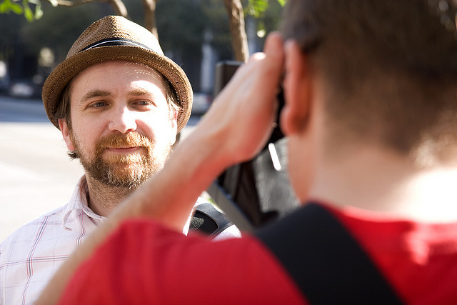 Scott (with beard and in hat) has his picture taken by man out-of-focus in foreground