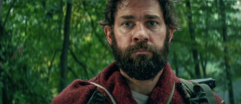 John Krasinski, in full beard and a red sweater, staring rather despairingly at us