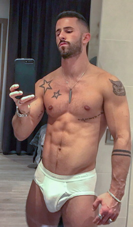 Shirtless musclegay (with some tattoos) taking mirror selfie in gym