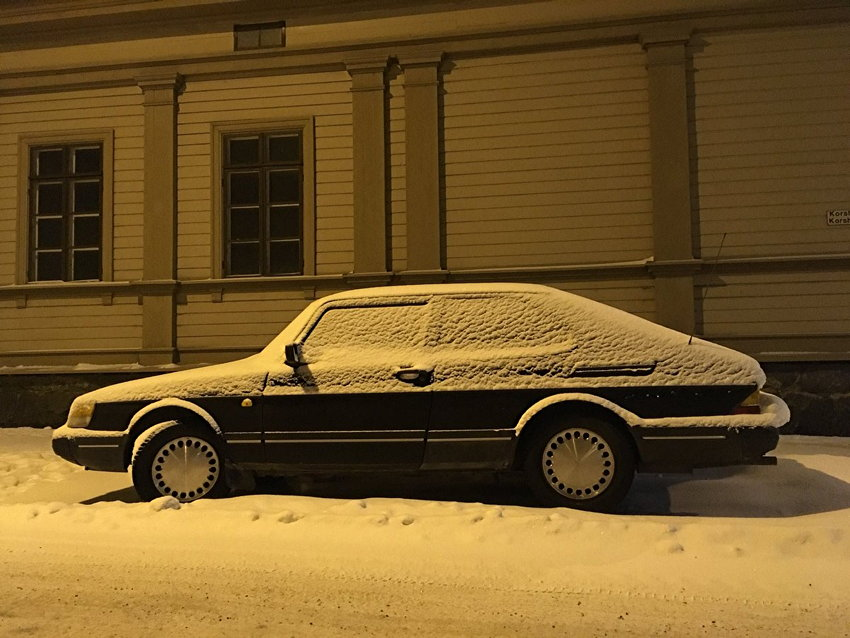 Black Saab 900, dusted in snow, sits on snow-covered road at the side of a building, all tinted amber by streetlight