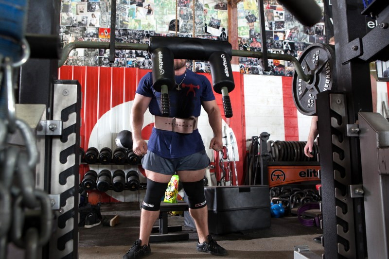 Hghly muscled man in blue shirt, shorts, kneepads, and weight belt has his face obscured behind pads on a weight bar