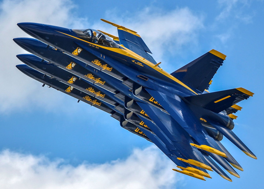 Four fighter jets, navy blue with yellow trim, seemingly stacked on each other in mid-air