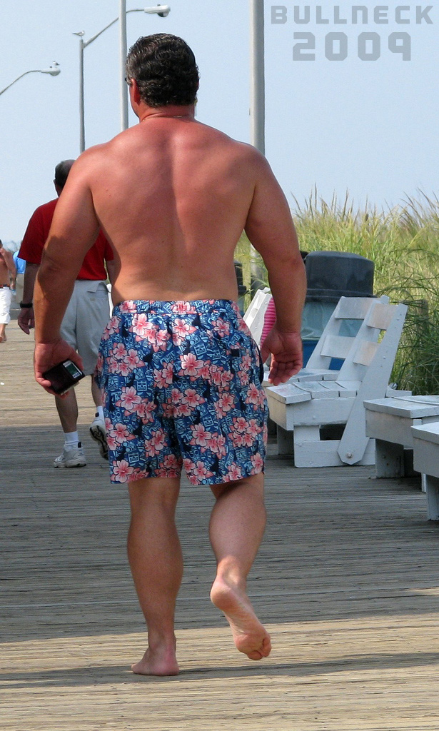 Muscular middle-aged male, with a bit of a sunburn, walks shirtless on a boardwalk