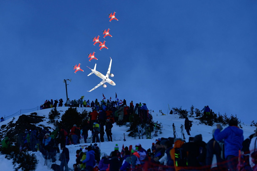 White commercial aircraft and six red-and-white fighter jets bank up and away from us into a deep indigo sky