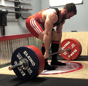 Very fit male (with beard) in singlet beginning a deadlift