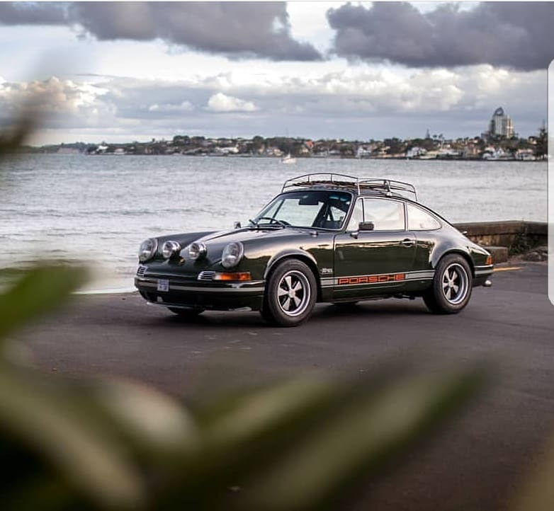 Green 911 with extra rally headlamps and roof rack parked along shore