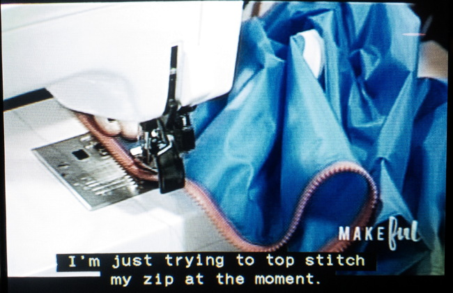 "Blue anorak with red zipper in sewing machine. ""I'm just trying to top-stitch my zip at the moment"""