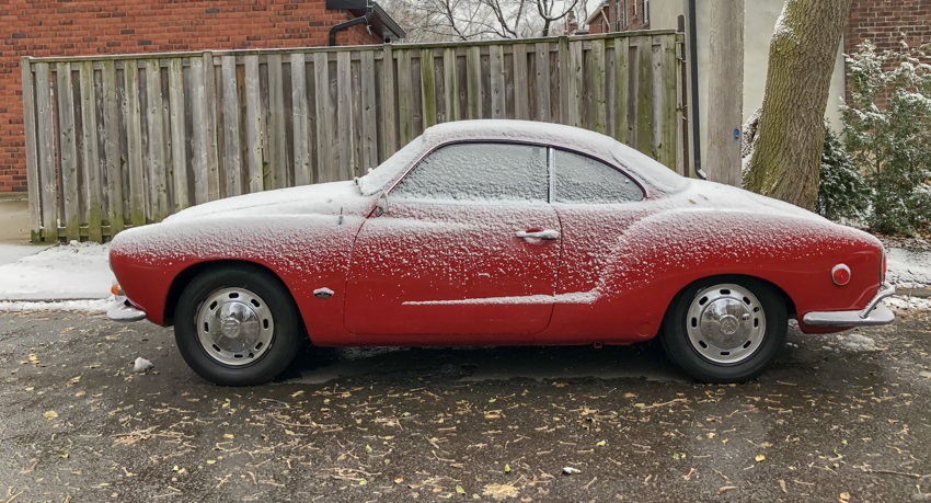 Red Karmann Ghia, uniformly dappled with snow on top surfaces, parked in front of angled fence