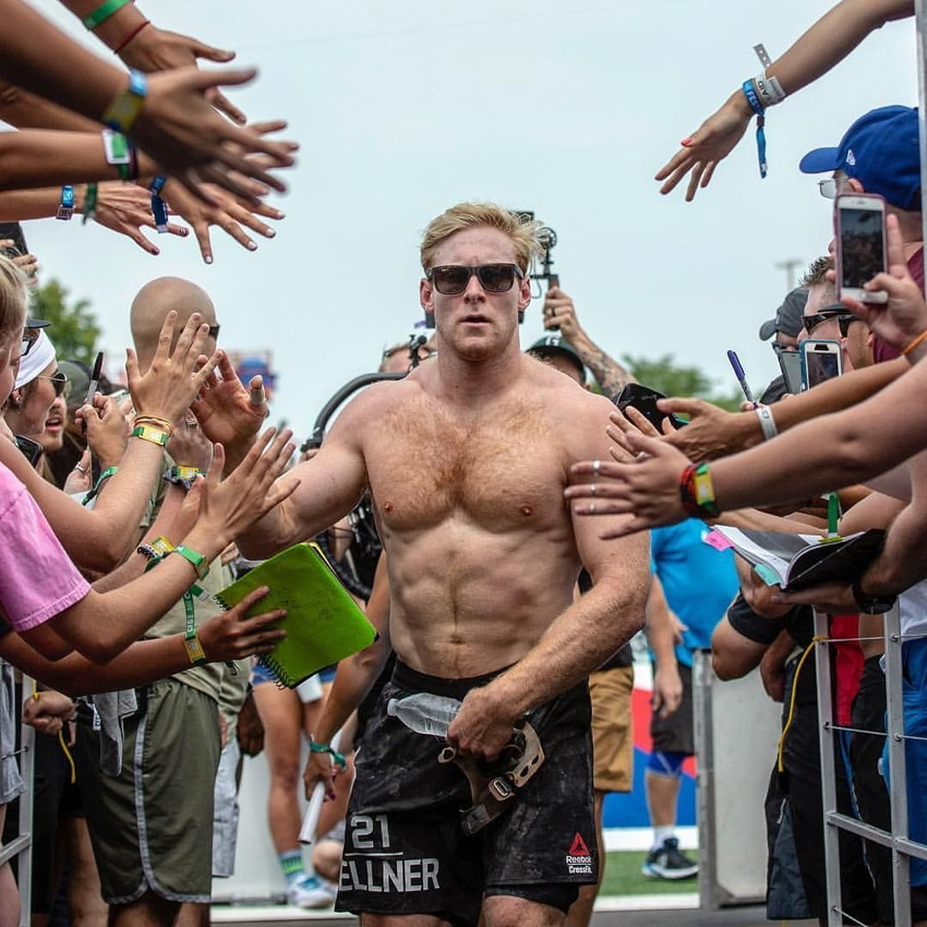 Shirtless ginger in shorts stares right at us through his shades with well-wishers behind fences on both sides