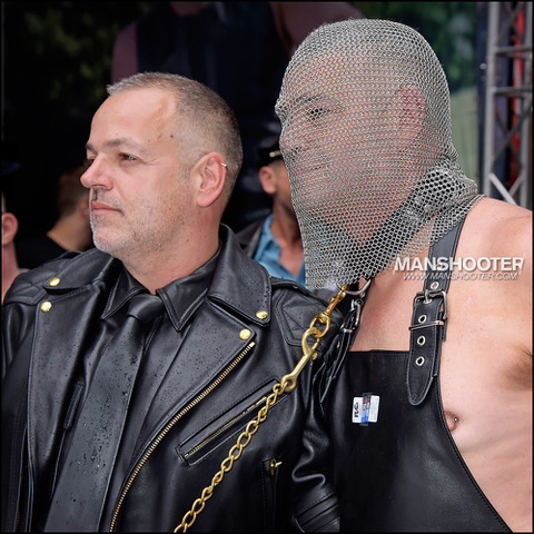 Two men, one shirtless in leather apron, on a leash, and wearing chain mail draped over head