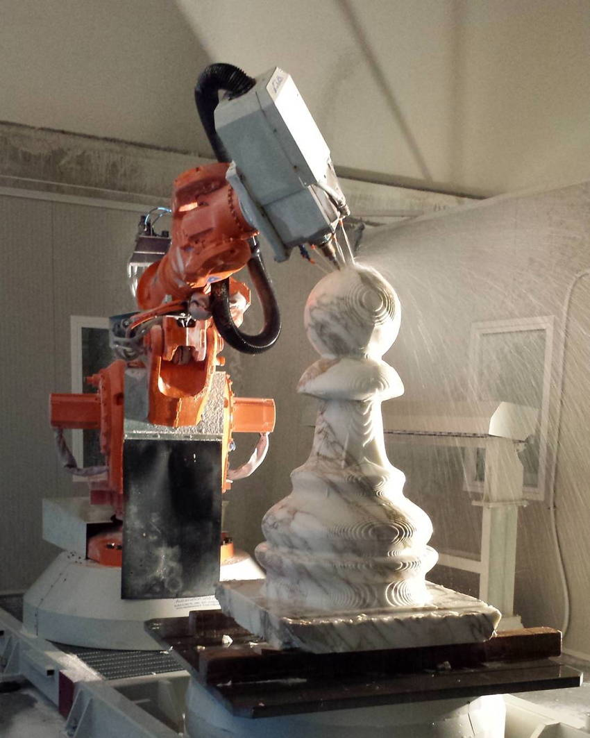 Lathe attachment on lobster-coloured industrial robot drills the spherical tip of a huge marble pawn