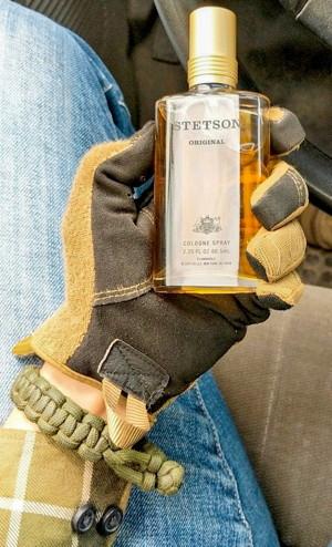 Gloved hand at steering wheel holding Stetson bottle